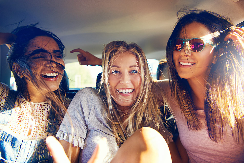 A group of teenage girls, smiling and having fun while riding as passengers in a car